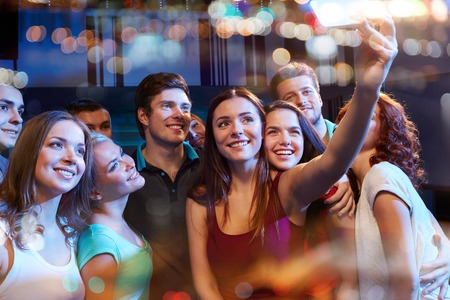 Photo for party, technology, nightlife and people concept - smiling friends with smartphone taking selfie in club - Royalty Free Image