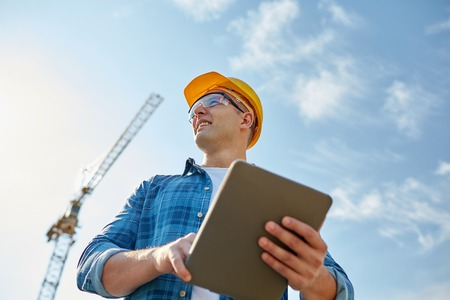 Foto de business, building, industry, technology and people concept - smiling builder in hardhat with tablet pc computer over group of builders at construction site - Imagen libre de derechos