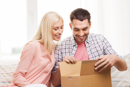 Foto für people, delivery, shipping and postal service concept - happy couple opening cardboard box or parcel at home - Lizenzfreies Bild