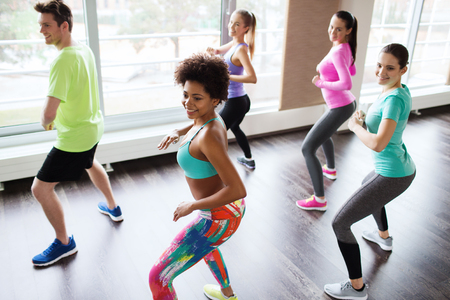 Foto de fitness, sport, dance and lifestyle concept - group of smiling people with coach dancing zumba in gym or studio - Imagen libre de derechos