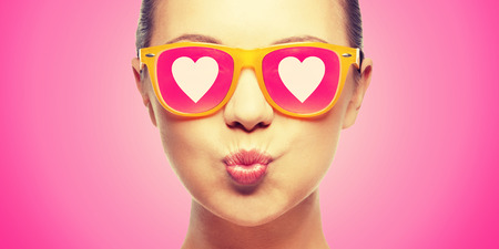 Photo for love, happiness, valentines day, face expressions and people concept - portrait of teenage girl in pink sunglasses with hearts blowing kiss - Royalty Free Image