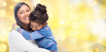 Photo for people, motherhood, family, holidays and adoption concept - happy mother and daughter hugging over yellow lights background - Royalty Free Image