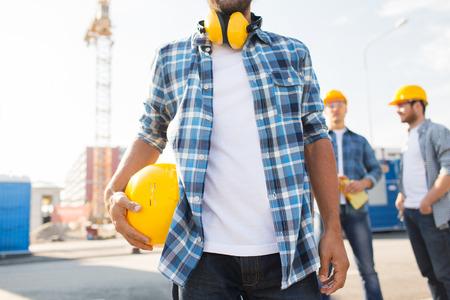 Photo pour close up of builder holding yellow hardhat or helmet outdoors - image libre de droit