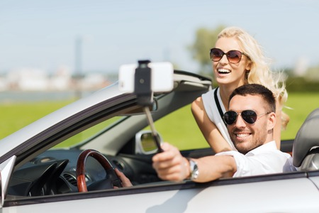 Photo pour road trip, leisure, couple, technology and people concept - happy man and woman driving in cabriolet car and taking picture with smartphone on selfie stick - image libre de droit