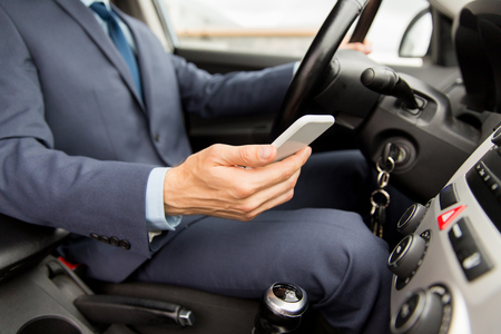 Photo pour transport, business trip, technology and people concept - close up of young man with smartphone driving car - image libre de droit