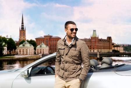 Photo for travel, tourism, road trip, transport and people concept - happy man near cabriolet car over city of stockholm in sweden background - Royalty Free Image