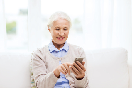 Photo pour technology, communication age and people concept - happy senior woman with smartphone texting message at home - image libre de droit