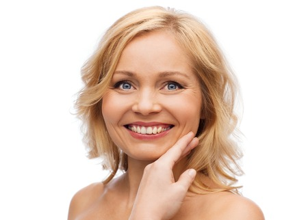 beauty, people and skincare concept - smiling woman with bare shoulders touching face