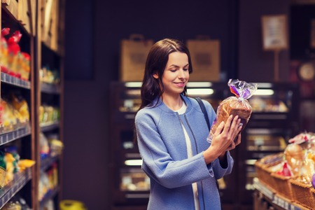Photo pour sale, shopping, consumerism and people concept - happy young woman choosing and reading label on bread in market - image libre de droit