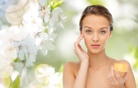 Foto de beauty, people, cosmetics, skincare and cosmetics concept - young woman applying cream to her face over green natural background with cherry blossom - Imagen libre de derechos