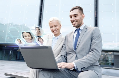Photo for business, communication, technology and people concept - smiling businesspeople making video call or conference with laptop computer on city street - Royalty Free Image
