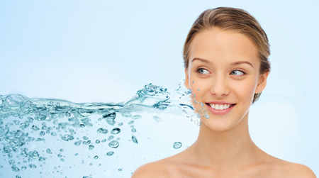 Photo for beauty, people and health concept - smiling young woman face and shoulders over water splash and blue background - Royalty Free Image