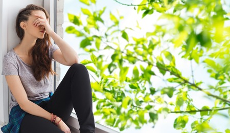 Photo for people, emotion and teens concept - sad unhappy pretty teenage girl sitting on windowsill over summer tree brunch background - Royalty Free Image