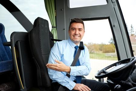 Foto de transport, tourism, road trip, gesture and people concept - happy driver inviting on board of intercity bus - Imagen libre de derechos