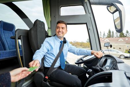 Foto de transport, tourism, road trip and people concept - smiling bus driver taking ticket or plastic card from passenger - Imagen libre de derechos