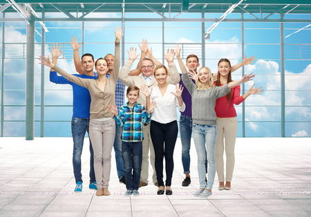 Photo pour travel, vacation and people concept - group of happy people or big family waving hands over airport terminal window and sky background - image libre de droit
