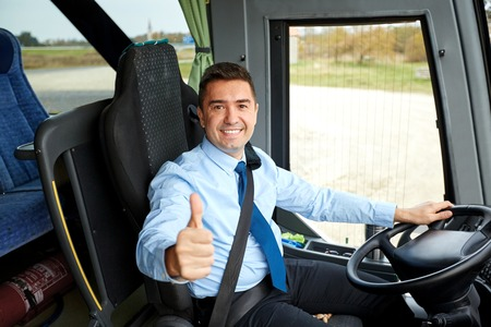 Photo for transport, tourism, road trip and people concept - happy driver driving intercity bus and snowing thumbs up - Royalty Free Image