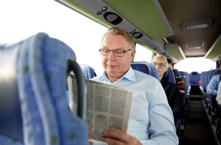 transport, tourism, trip and people concept - senior man reading newspaper in travel bus