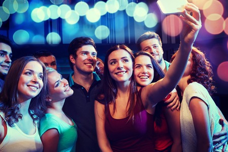 Photo pour party, technology, nightlife and people concept - smiling friends with smartphone taking selfie in club - image libre de droit