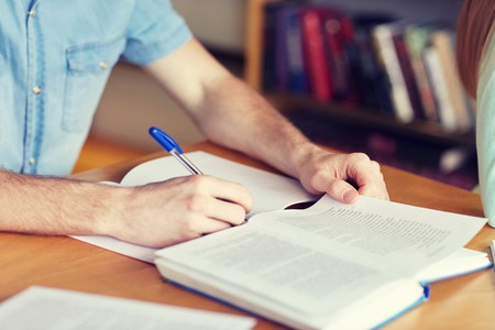 Photo pour people, learning, education and school concept - close up of student boy hands with book or textbook writing to notebook at library - image libre de droit
