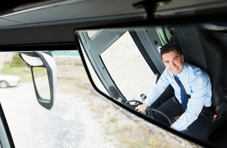 Photo for transport, transportation, tourism, road trip and people concept - close up of smiling driver reflection in passenger bus mirror - Royalty Free Image