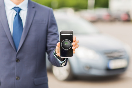 transport, business trip, technology and people concept - close up of man showing smartphone with ignition starter remote control application on screen on car parking