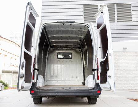 Foto de freight transportation, logistics, transport and vehicle concept - white empty minivan car with open doors on city parking - Imagen libre de derechos