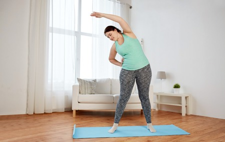 Photo for fitness, sport, exercising, training and lifestyle concept - smiling plus size woman stretching on mat at home - Royalty Free Image