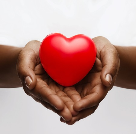 Photo pour health, medicine and charity concept - close up of african american female hands with small red heart - image libre de droit