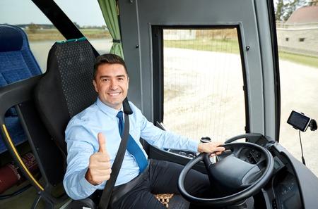 Photo pour transport, tourism, road trip and people concept - happy driver driving intercity bus and snowing thumbs up - image libre de droit
