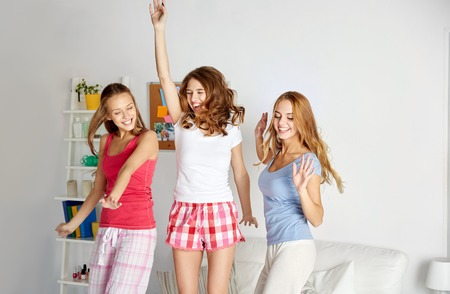 friendship, people and pajama party concept - happy friends or teenage girls having fun, dancing and jumping on bed at homeの写真素材