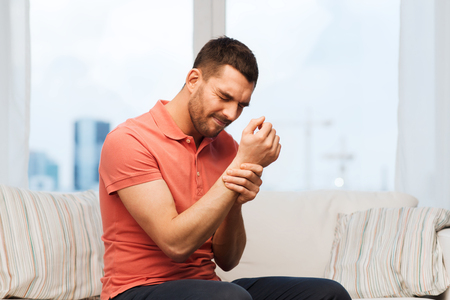 people, healthcare and problem concept - unhappy man suffering from pain in hand at home