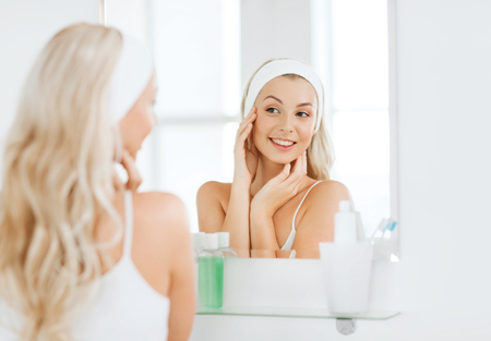 beauty, skin care and people concept - smiling young woman in hairband touching her face and looking to mirror at home bathroomの写真素材