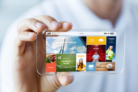 Photo pour business, technology and people concept - close up of male hand holding and showing transparent smartphone news web page on screen - image libre de droit