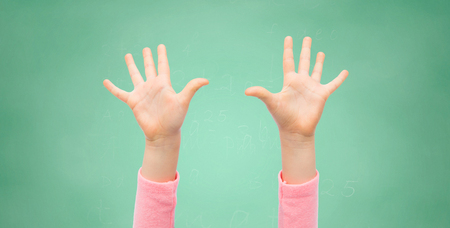 Photo pour people, childhood, gesture, education and body parts concept - close up of little child hands raised up over green school chalk board background - image libre de droit