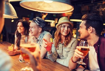 Foto de people, leisure, friendship and communication concept - group of happy smiling friends drinking beer and cocktails talking at bar or pub - Imagen libre de derechos