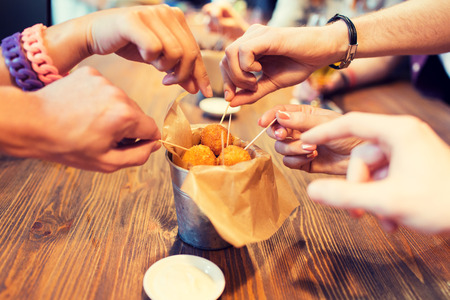 Photo pour fast food, junk food, unhealthy eating and culinary concept - close up of people hands taking cheese balls with skewers at bar or restaurant - image libre de droit