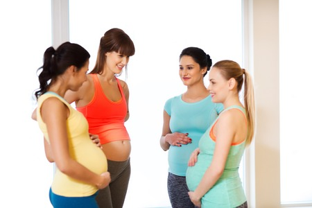 pregnancy, sport, fitness, people and healthy lifestyle concept - group of happy pregnant women talking in gymの写真素材