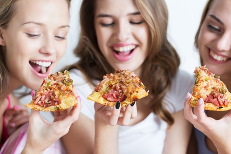 Photo pour friendship, people, pajama party and junk food concept - close up of happy friends or teenage girls eating pizza at home - image libre de droit
