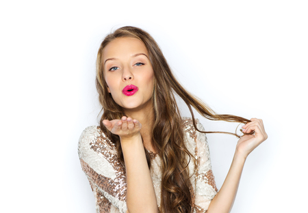 people, style, holidays, hairstyle and fashion concept - happy young woman or teen girl in fancy dress with sequins and long wavy hair sending blow kiss