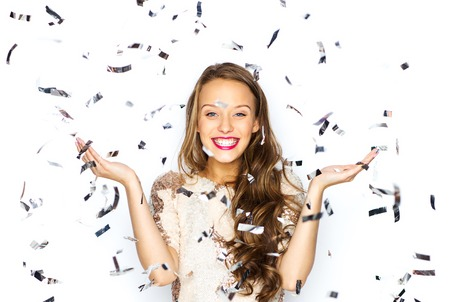 Foto de people, holidays, emotion and glamour concept - happy young woman or teen girl in fancy dress with sequins and confetti at party - Imagen libre de derechos