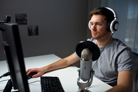 technology, gaming, entertainment, let\'s play and people concept - young man in headset with pc computer playing game at home and streaming playthrough or walkthrough video