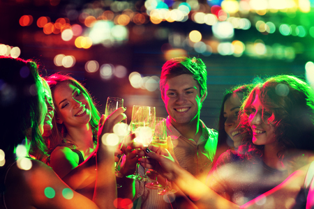 Foto de party, holidays, celebration, nightlife and people concept - smiling friends clinking glasses of champagne in night club with holidays lights - Imagen libre de derechos