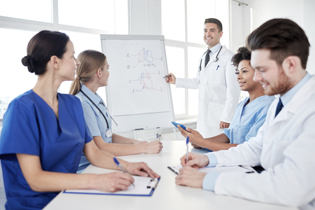 Photo for medical education, health care, medical education, people and medicine concept - group of happy doctors or interns with mentor meeting and drawing on flip board on presentation at hospital - Royalty Free Image