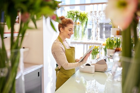 Photo for people, business, technology, sale and floristry and concept - happy smiling florist woman with tablet pc computer at flower shop - Royalty Free Image