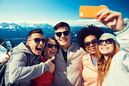 Photo pour people, travel, tourism, friendship and technology concept - group of happy teenage friends taking selfie with smartphone and showing thumbs up over alps mountains in austria background - image libre de droit