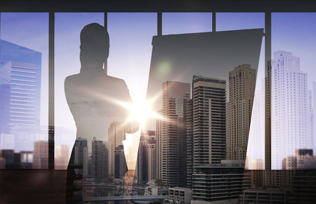 business, strategy, planning and people concept - silhouette of woman with flipboard over double exposure office and city background