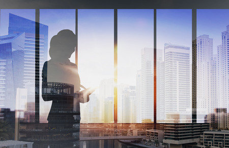 Photo pour business and people concept - silhouette of woman with tablet pc over office window background over double exposure office and city background - image libre de droit