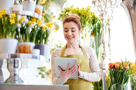 Photo for happy smiling florist woman with tablet pc computer at flower shop - Royalty Free Image