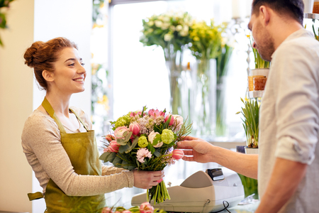 Photo pour happy smiling florist woman making bouquet for and man or customer at flower shop - image libre de droit